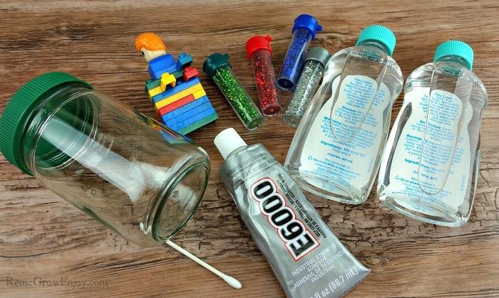Supplies to make a LEGO snow globe, e600, qtip, glitter, mineral oil, legos and a jar.