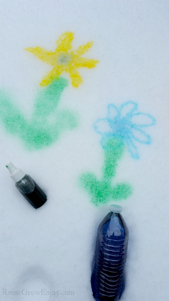 A yellow flower and blue flower painted on snow with a spray bottle and water bottle full of snow paint.