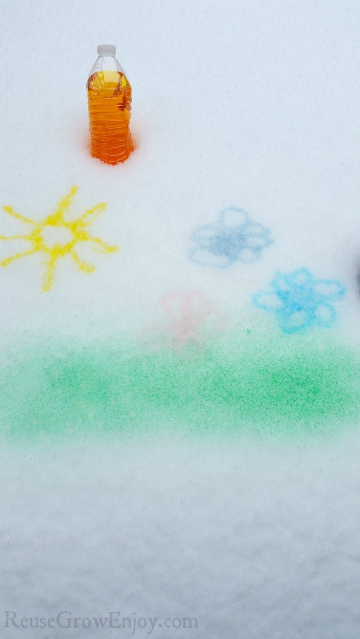 Sun, flowers and grass painted on snow with a bottle of dark yellow snow paint at the top.