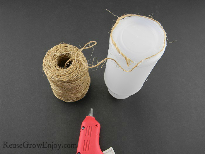 Small plastic bottle being wrapped in twine and glued with hot glue gun