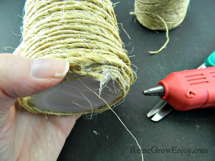 Cut the twine spool from the bottle and use hot glue to attach to bottom of bottle