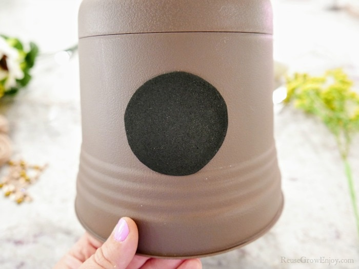 Stick black sticker to side of flower pot
