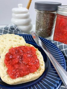 Strawberry jam on a english muffin on blue plate with jar of jam in background