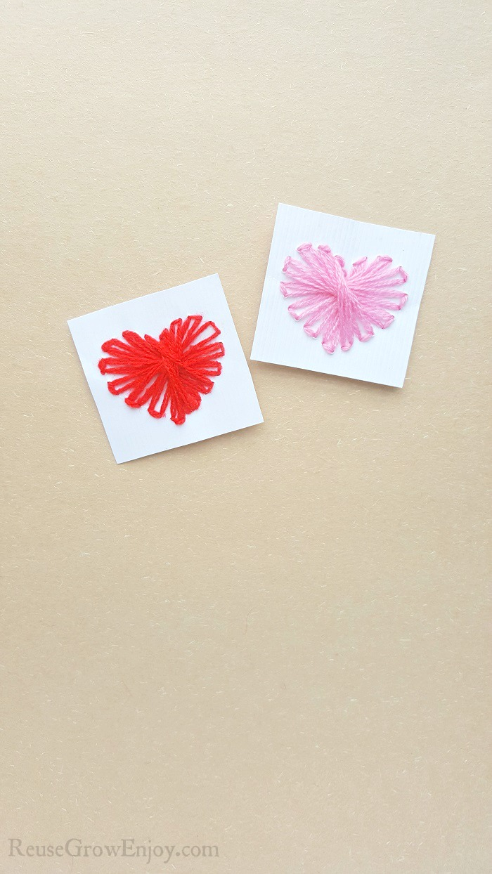 String heart craft made on white cardstock paper one heart has pink thread the other has red. Both laying on a brown paper background.