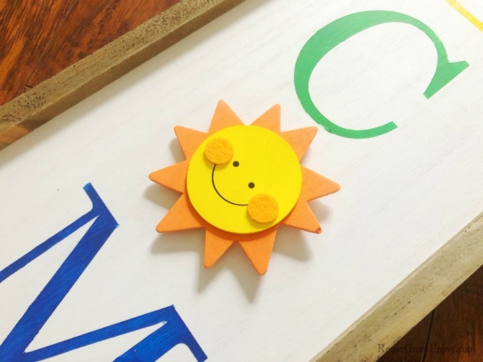 Wood sun attached to welcome sign