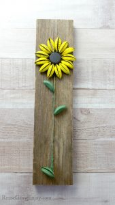 Finished bottle cap sunflower on wood