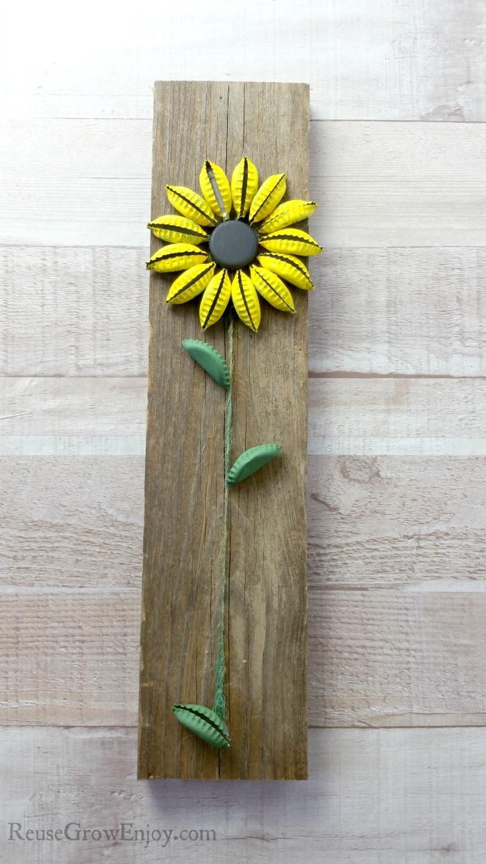 Finished bottle cap sunflower on wood