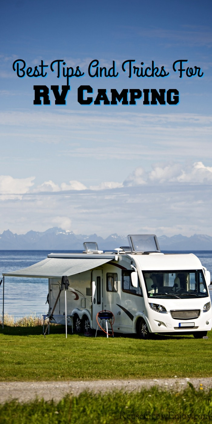 RV camping by water with green grass around it. Text overlay on the top that says Best Tips And Tricks For RV Camping
