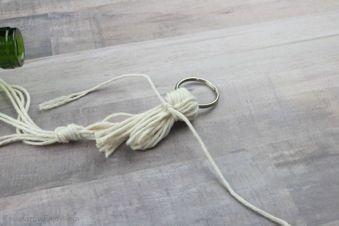Tie a knot around the loose string.