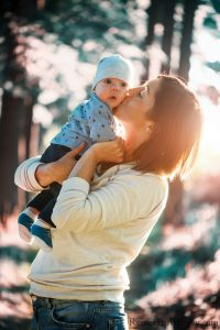 Mom holding and kissing baby in woods with sun setting