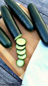 Fresh garden cucumbers on a wood cutting board with one half sliced up - Tips On How To Grow Cucumbers