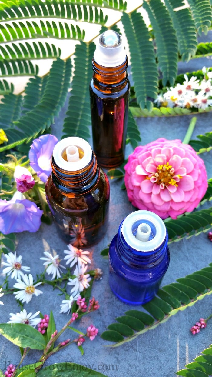 Bottles of Essential Oils for Fibromyalgia with bright pretty flowers all around
