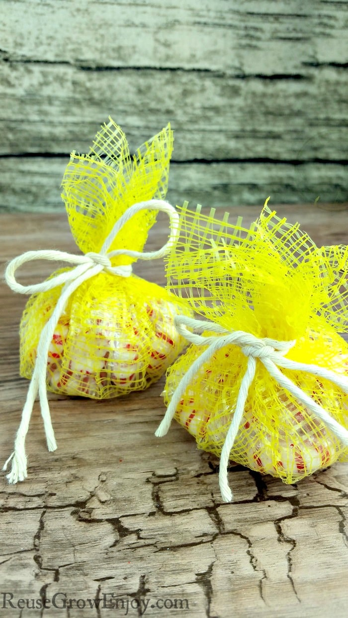 Yellow mesh produce bags made into treat bags with wood background.