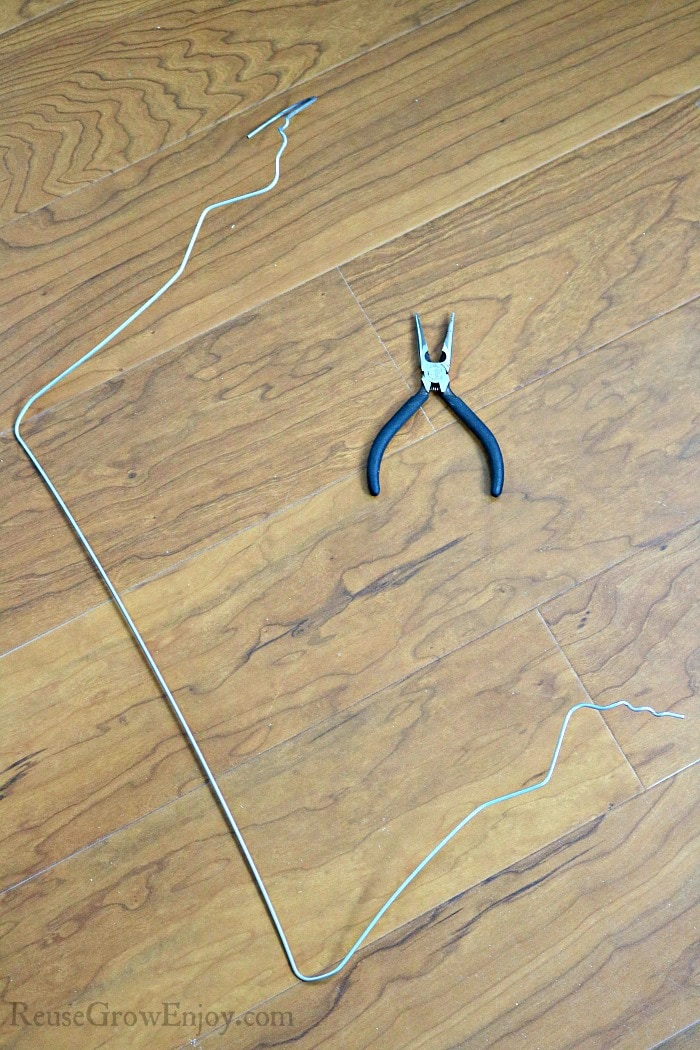 Coat hanger un twisted with pliers laying next to it
