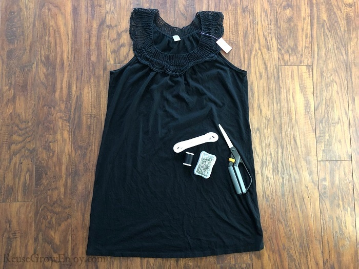 Small black tank style dress on wood floor with scissors, thread, pins and elastic laying on top of it.