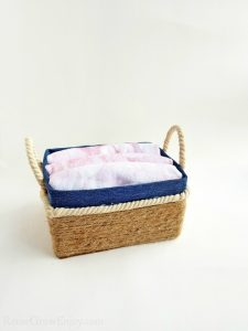 Small rope basket with rope handles full of folded cloth.