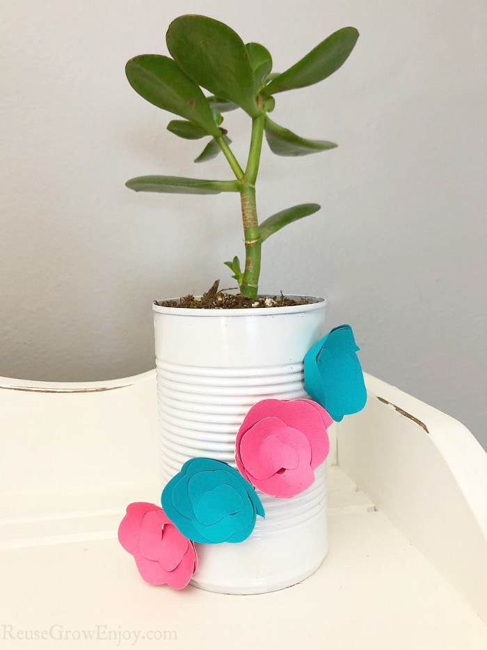 Upcycled can planter that is white with blue and pink paper flowers on it with plant inside. Sitting on a white wood shelf.