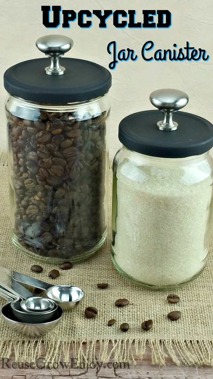 Two glass jars that have been turned into upcycled jar canister with stainless steel knobs on top. One jar is filled with coffee beans and the other with raw sugar.