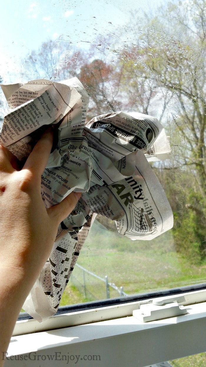 Hand holding bunched up newspaper wiping the window with it.