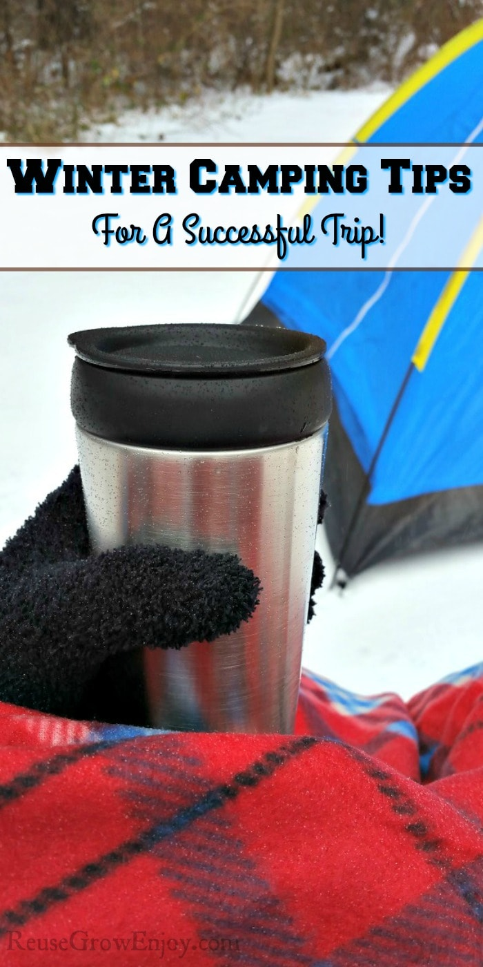 "Snow on ground with tent in the background and a hand with a black glove holding a stainless steel mug and covered in red plaid blanket with a text overlay that says ""Winter Camping Tips For A Successful Trip""."