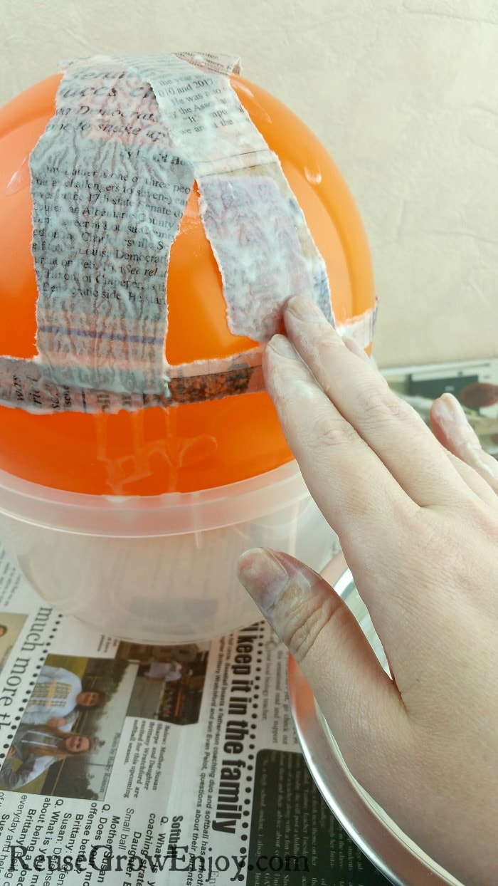 Hand placing dipped newspaper strips on balloon.
