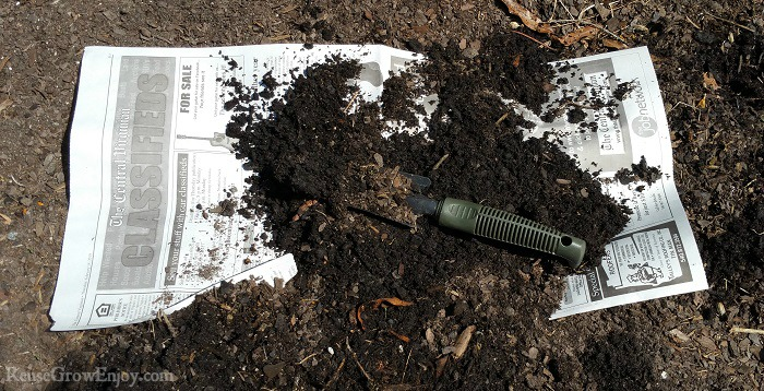 Newspaper being covered with soil in the garden.