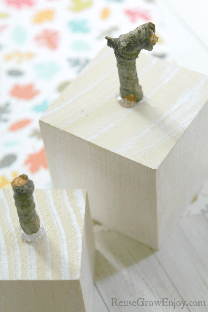 Twigs hot glued to top of white wood blocks.